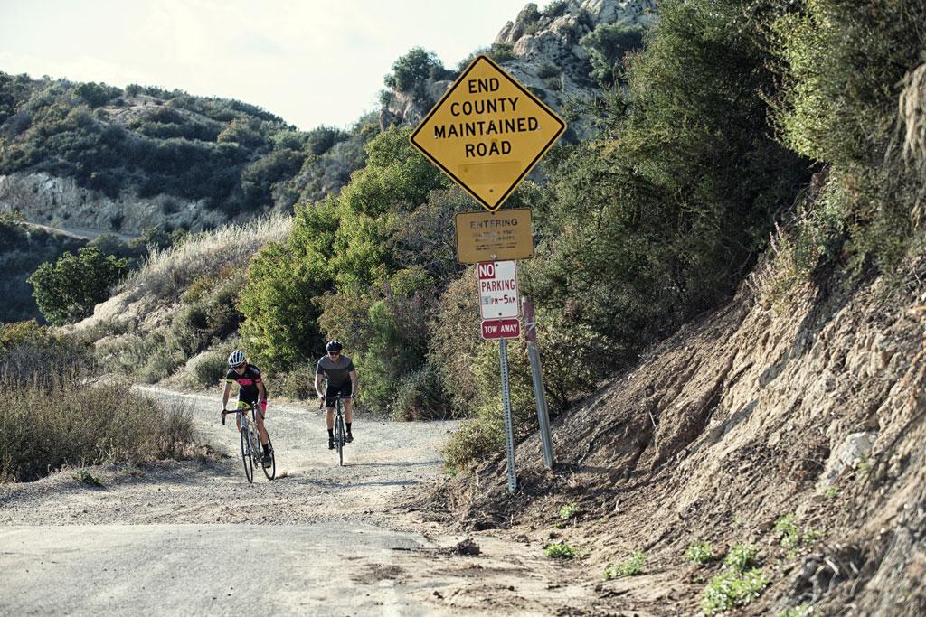 Pareja montando en bici de gravel por pistas de tierra