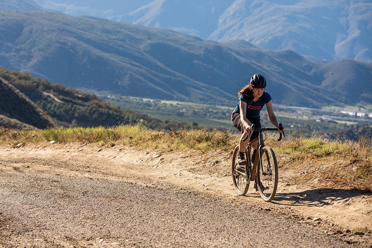 Foto de acción de una mujer montando en gravel por pistas de tierra