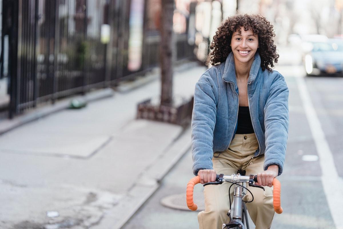 Ciclista urbana sonriendo en la ciudad