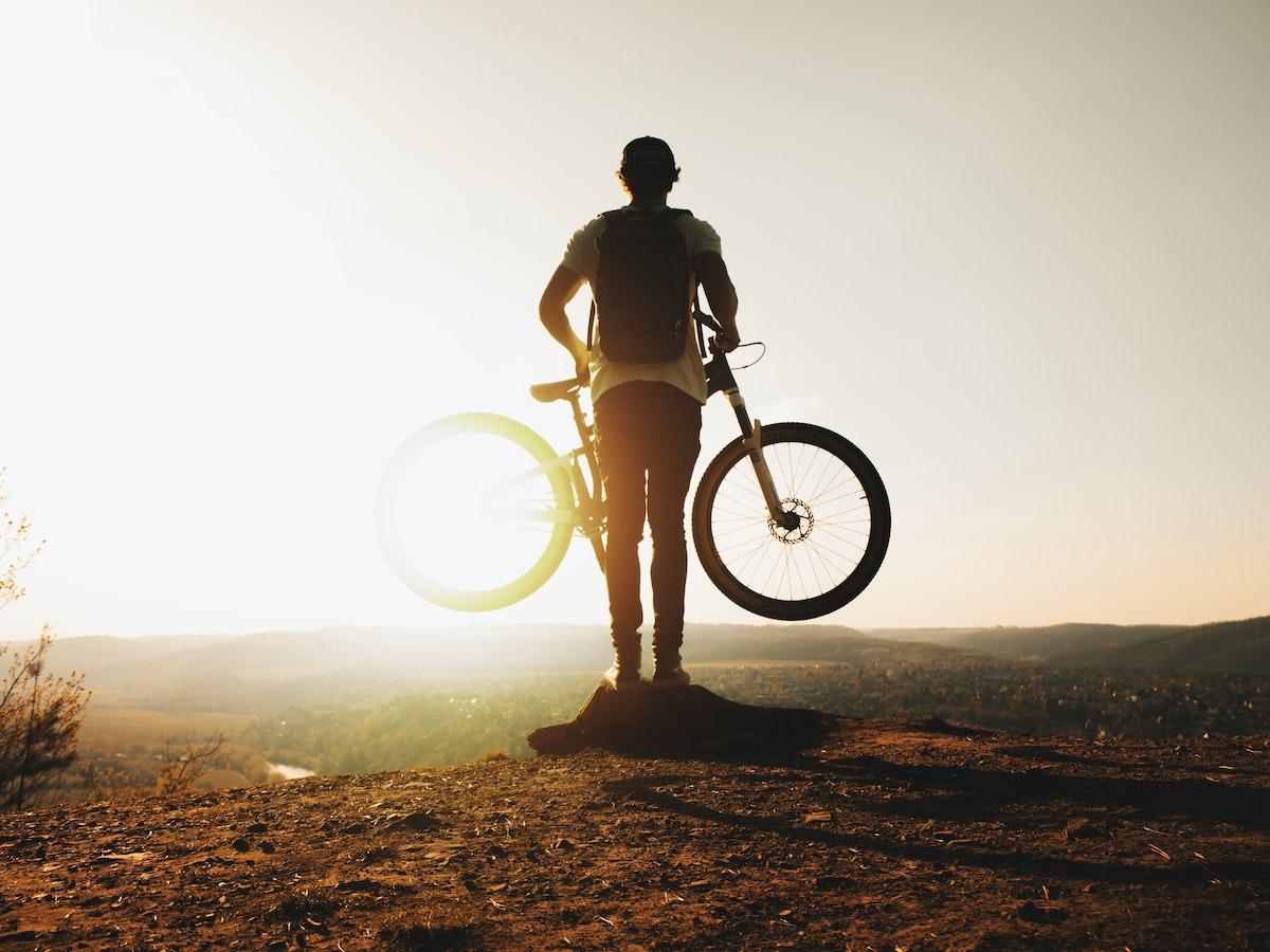 Hombre observando un atardecer con su bicicleta