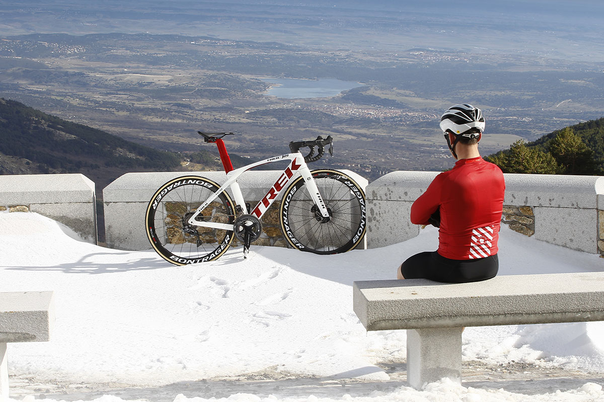 Foto estática de un ciclista contemplando la bici con las nieves del invierno