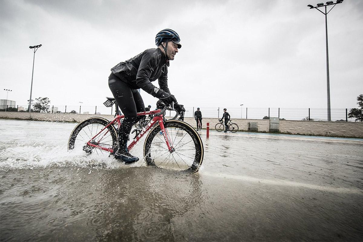 Foto de acción en bici de carretera con el asfalto anegado de agua